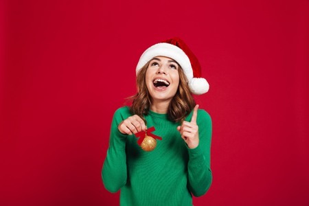 Photo of young emotional woman wearing christmas santa hat standing isolated over burgundy background looking aside holding christmas tree toys decorations pointing. 版權商用圖片