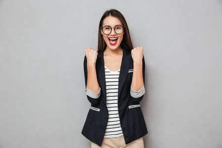 Happy screaming asian business woman in eyeglasses rejoices and looking at the camera over gray background