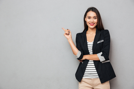 Smiling asian business woman pointing up and looking at the camera over gray background Stockfoto