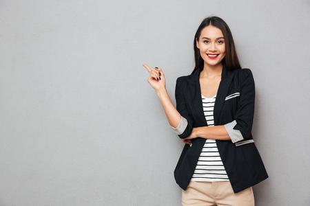 Mulher de negócios asiáticos sorridente apontando para cima e olhando para a câmera sobre fundo cinza Foto de archivo - 94123301