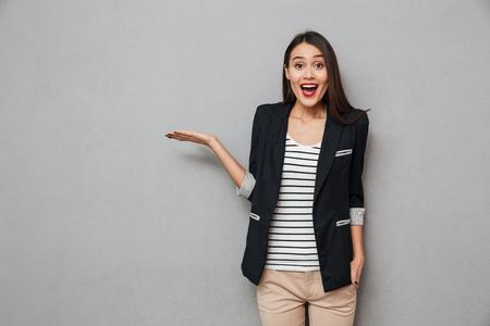 Surpresa feliz negócios asiáticos mulher segurando copyspace na palma da mão e olhando para a câmera sobre fundo cinza