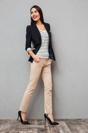 Full length image of Cheerful asian business woman walking with arms in pockets and looking back over gray background Foto de archivo