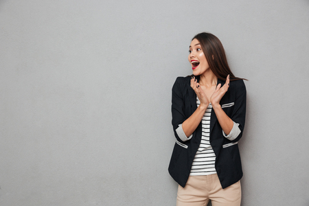 Surprised happy asian business woman screaming and looking away over gray background