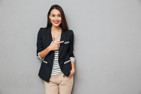 Smiling asian business woman with arm in pocket pointing away and looking at the camera over gray background 免版税图像