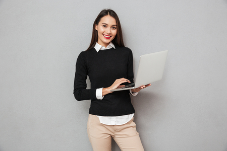 Smiling asian woman in business clothes using laptop computer while looking at the camera over gray background Imagens