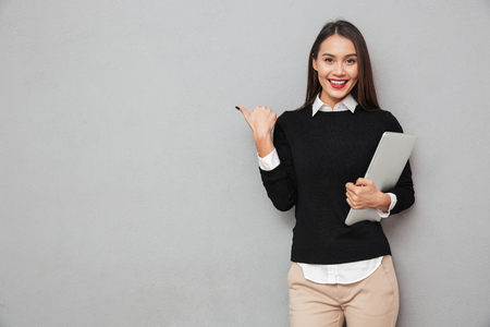 Smiling asian woman in business clothes holding laptop computer and pointing at copyspace while looking at the camera over gray background