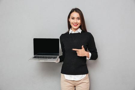 Erfreute asiatische Frau in der Geschäftskleidung , die leeres Laptop-Computer zeigt und auf ihm zeigt , während die Kamera über grauem Hintergrund schaut