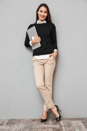 Full length image of Pleased asian woman in business clothes holding laptop computer while looking at the camera over gray background