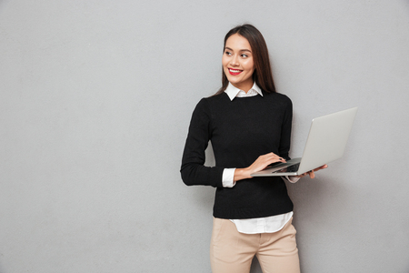 Pleased asian woman in business clothes holding laptop computer while looking away over gray background