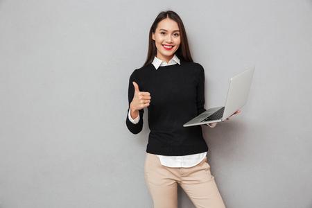 Mujer asiática contenta en la ropa del negocio que sostiene el ordenador portátil y que muestra el pulgar para arriba mientras que mira la cámara sobre fondo gris