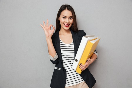 Mujer de negocios asiática sonriente que sostiene carpetas y que muestra la muestra aceptable mientras que mira la cámara sobre fondo gris