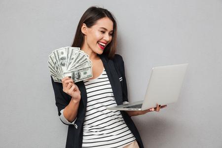 Mujer de negocios asiática feliz que sostiene el dinero y el ordenador portátil sobre fondo gris