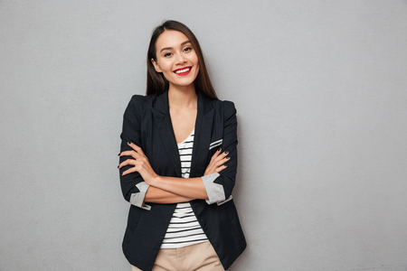 Pleased asian business woman with crossed arms looking at the camera over gray background Stockfoto