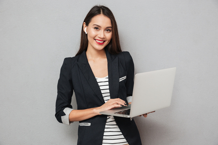 Happy asian business woman holding laptop computer and looking at the camera over gray background