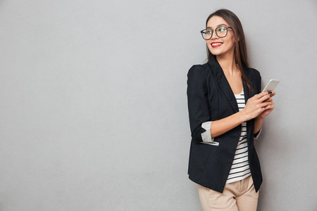 Smiling asian business woman in eyeglasses holding smartphone and looking back over gray background Stock Photo - 94256709