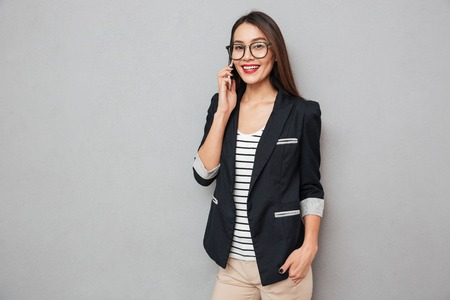 Pleased asian business woman in eyeglasses talking by smartphone and looking at the camera over gray background Stockfoto