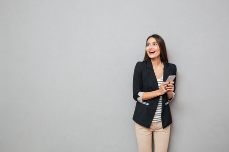 Cheerful asian business woman holding smartphone and looking away over gray background