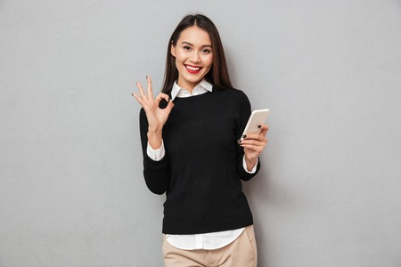 Pleased asian woman in business clothes holding smartphone and showing ok sign while looking at the camera over gray background