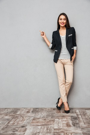 Full length image of Happy asian business woman pointing on copyspace and looking at the camera with arm in pocket over gray background