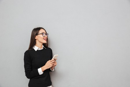 Happy asian woman in business clothes and eyeglasses holding smartphone and looking away over gray background