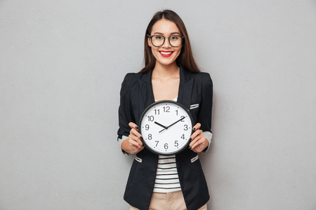 Smiling asian business woman in eyeglasses holding clock and looking at the camera over gray background