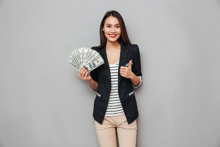 Pleased asian business woman holding money and showing thumb up while looking at the camera over gray background