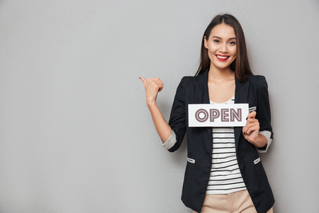 Pleased asian business woman holding nameplate open and pointing on copyspace while looking at the camera over gray background