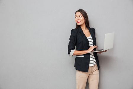 Lächelnde asiatische Geschäftsfrau , die Laptop-Computer hält und zurück über grauem Hintergrund schaut Standard-Bild