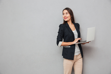 sonriente mujer de negocios asiática sosteniendo la computadora portátil y mirando hacia atrás sobre fondo gris Foto de archivo