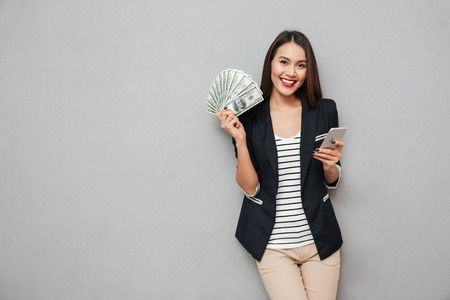 Happy asian business woman holding smartphone and money while looking at the camera over gray background