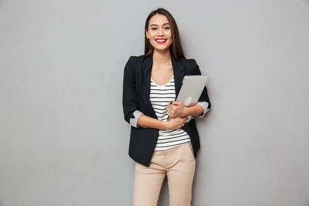Pleased asian business woman holding laptop computer and looking at the camera over gray background