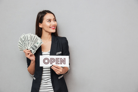 Happy asian business woman holding nameplat open and money while looking away over gray background