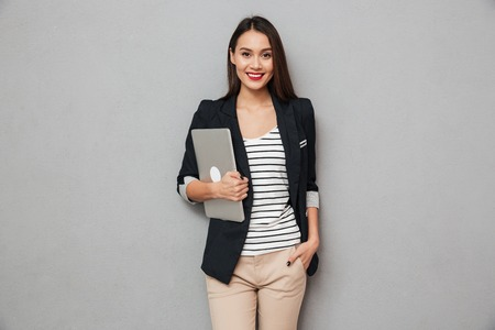 Smiling asian business woman with arm in pocket holding laptop computer and looking at the camera over gray background
