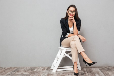 Smiling asian business woman in eyeglasses sitting on chair and looking at the camera over gray background Foto de archivo