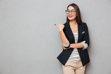 Smiling asian business woman in eyeglasses pointing and looking away over gray background