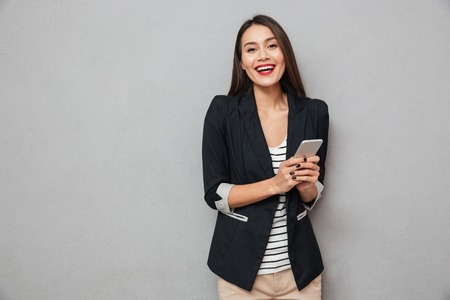 Happy asian business woman holding smartphone and looking at the camera over gray background