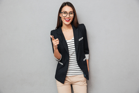 Joyful asian business woman in eyeglasses pointing and looking at the camera over gray background