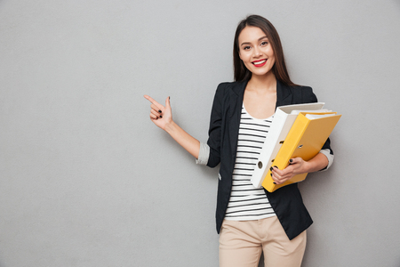 Pleased asian business woman with folders pointing on copyspace and looking at the camera over gray background Banco de Imagens