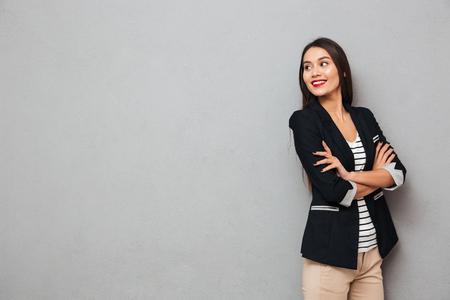 Gelukkige Aziatische bedrijfsvrouw die met gekruiste wapens weg over grijze bakground kijkt Stockfoto - 94076114