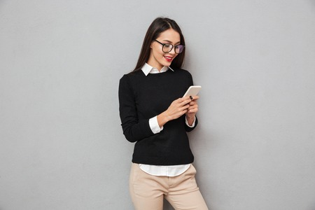 Smiling asian woman in business clothes and eyeglasses writing message on smartphone over gray background