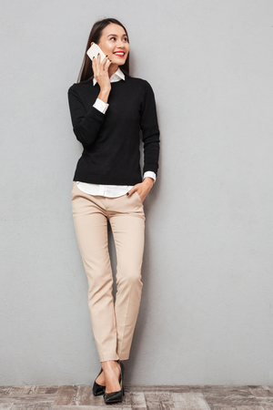 Full length image of Smiling asian woman in business clothes talking by smartphone and looking away over gray background