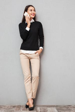 Volledig lengtebeeld van Glimlachende Aziatische vrouw in bedrijfskleren die door smartphone spreken en weg over grijze achtergrond kijken Stockfoto - 93811593