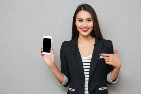 Smiling asian business woman showing blank smartphone screen and pointing on him while looking at the camera over gray background