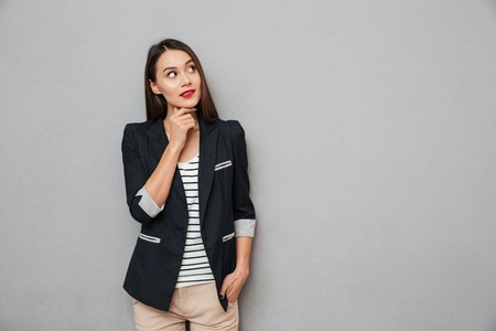 Pensive asian business woman with arm in pocket holding her chin and looking away over gray background