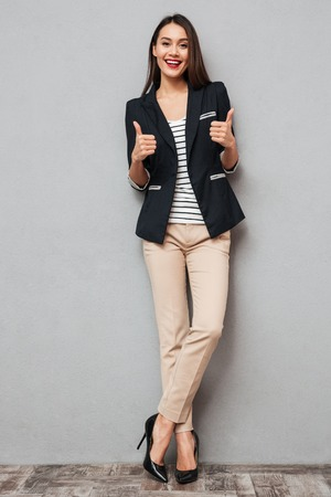 Full length image of Cheerful asian business woman showing thumbs up and looking at the camera over gray background