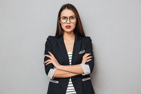 Serious asian business woman in eyeglasses with crossed arms looking at the camera over gray background Stock Photo