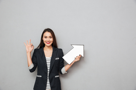 Smiling asian business woman showing ok sign and pointing with paper arrow up while looking at the camera over gray background Foto de archivo