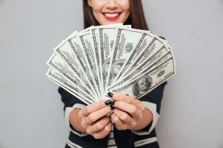 Cropped image of smiling asian business woman showing money at the camera over gray background