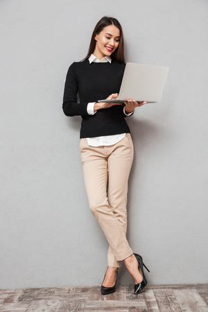 Full length image of Smiling asian woman in business clothes using laptop computer over gray background