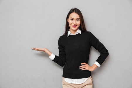 Smiling asian woman in business clothes with arm on hip holding copyspace on the palm while looking at the camera over gray background